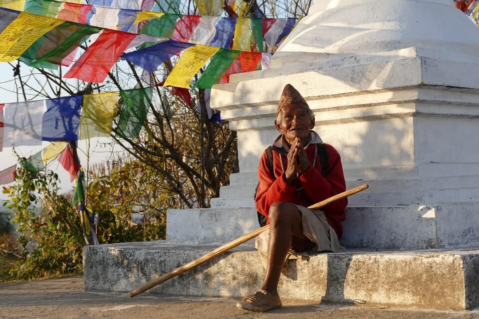 Kathmandu vallei trekking – begroeting door een oude man aan het klooster van Namobuddha