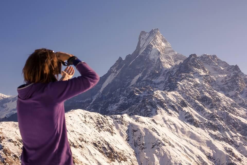 Mardi Himal trekking – vrouwelijke wandelaar geniet van uitzicht op de besneeuwde Machapuchare